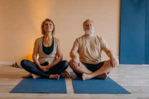זוג קשישים עושה יוגה בישיבה